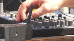 Mens die aan professionele digitale audiokanaalmixer werken De elektronika voor versterker en het saldo van geluid in tonen stock footage