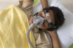 Mens die aan Slaap Apnea lijden, die een CPAP-machine met behulp van Stock Foto