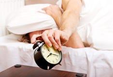 Mens die aan slaap proberen, wanneer wekker het bellen Stock Foto's