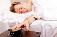 Mens die aan slaap proberen, wanneer wekker het bellen Royalty-vrije Stock Foto's