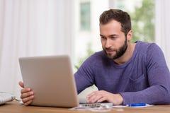 Mens die aan zijn laptop computer thuis werkt