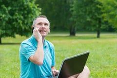 Mens die aan zijn laptop in het park werkt Stock Afbeelding