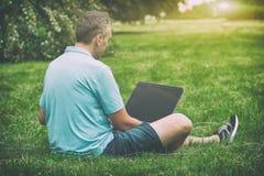 Mens die aan zijn laptop in het park werkt royalty-vrije stock afbeeldingen