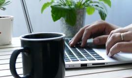 Mens die aan zilveren laptop met kop van koffie en groene installatie werken royalty-vrije stock afbeelding