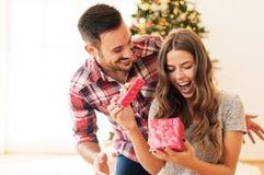 Mens die aanwezige Kerstmis geven aan zijn meisje Stock Afbeeldingen