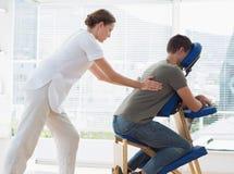 Mens die achtermassage van fysiotherapeut ontvangen Stock Foto
