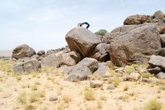 Mens die acrobatische bewegingen op een rots doen Royalty-vrije Stock Foto's