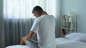 Mens die actief zijn verkleumde hals masseren, die pijn na slecht kwaliteitshoofdkussen voelen stock video