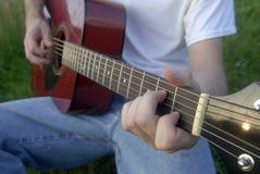 Mens die akoestische gitaar speelt Stock Afbeeldingen