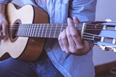 Mens die akoestische gitaar speelt Stock Foto's