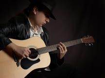 Mens die akoestische gitaar speelt bij rotsoverleg royalty-vrije stock foto