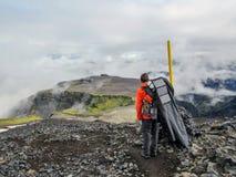 Mens die alleen in de wildernis wandelen die vulkanisch landschap met zware rugzak bewonderen Het concept van de het avonturenzwe stock afbeeldingen