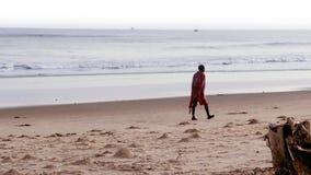 Mens die alleen op het strand lopen stock videobeelden