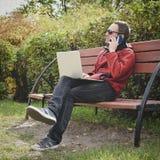 Mens die altijd in openlucht verbonden aan zijn smartphone en zijn loyale laptop werken jonge kerel, freelancer in openlucht werk royalty-vrije stock foto