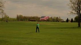 Mens die Amerikaanse vlag op een open plek golven stock footage