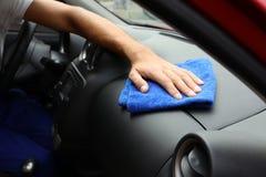 Mens die automobiel dashboard met stofdoek, close-up schoonmaken stock afbeelding