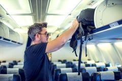 Mens die bagage op de hoogste plank op vliegtuig zetten royalty-vrije stock foto's