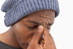 Mens die in beaniehoed met een hoofdpijn inekrimpen Stock Afbeelding