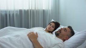 Mens die in bed, geërgerde vrouwenontwaken en duwende echtgenoot snurken, gezondheidsprobleem stock videobeelden