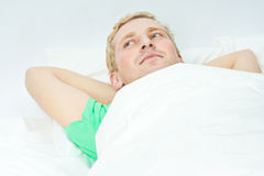 Mens die in bed het lachen ligt Royalty-vrije Stock Afbeeldingen