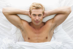 Mens die in bed het ontspannen ligt royalty-vrije stock afbeeldingen