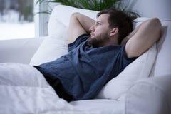 Mens die in bed ligt Stock Afbeelding