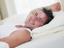 Mens die in bed ligt royalty-vrije stock afbeelding