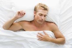Mens die in bed ligt royalty-vrije stock foto's