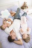 Mens die in bed met twee het jonge meisjes glimlachen ligt Royalty-vrije Stock Afbeeldingen