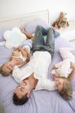 Mens die in bed met twee het jonge meisjes glimlachen ligt Stock Foto's