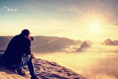 Mens die beeld van landschap het awaking in misttoerist nemen met camera en driepoot stock foto