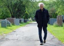 Mens die in begraafplaats loopt Stock Fotografie