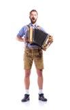 Mens die in Beierse kleren harmonika en het zingen spelen Oktoberfe royalty-vrije stock afbeelding
