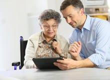 Mens die bejaarde dame onderwijzen hoe te om tablet te gebruiken Stock Foto