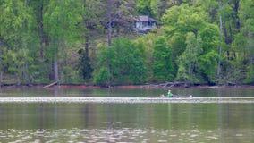 Mens die in bemanningsboot op meer met bomen op de achtergrond roeit royalty-vrije stock foto's