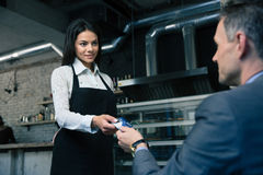 Mens die betaalpas geven aan vrouwelijke kelner Stock Fotografie