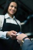 Mens die betaalpas geven aan vrouwelijke kelner in koffie Royalty-vrije Stock Afbeeldingen
