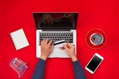 Mens die bij bureau en kopende producten online werken, online het winkelen concept stock foto's