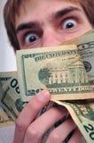 Mens die bij een pakje van contant geld staart royalty-vrije stock fotografie