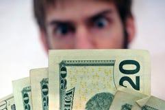 Mens die bij een pakje van contant geld staart Stock Fotografie