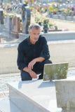 Mens die bij graf rouwen royalty-vrije stock fotografie