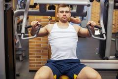 Mens die bij gymnastiek uitoefent Geschiktheidsatleet die borstoefeningen op de verticale machine van de bankpers doen stock afbeelding