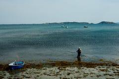 mens die bij het overzeese kuststrand vissen naast een kleine rubberboot voor een ankerplaats stock afbeeldingen