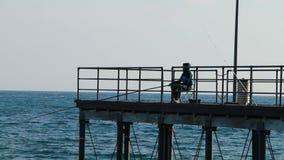 Mens die bij kust vissen stock videobeelden
