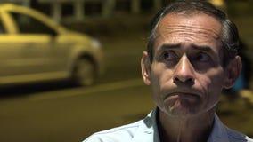 Mens die bij Nacht dichtbij Verkeer denken stock footage