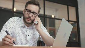 Mens die bij smartphone spreken en in bureau schrijven stock videobeelden