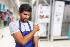 Mens die bij supermarkt werken die pijnlijke schouder houden stock foto
