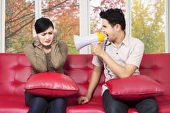 Mens die bij zijn vrouw schreeuwen die megafoon met behulp van Royalty-vrije Stock Fotografie