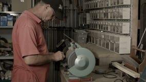Mens die binnen in afgeworpen hobby of workshop met de hulpmiddelen van de timmerwerkmacht werken stock videobeelden