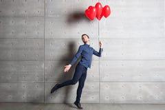 Mens die binnen op grijze muur als achtergrond met rode hart gevormde ballons springen royalty-vrije stock afbeeldingen